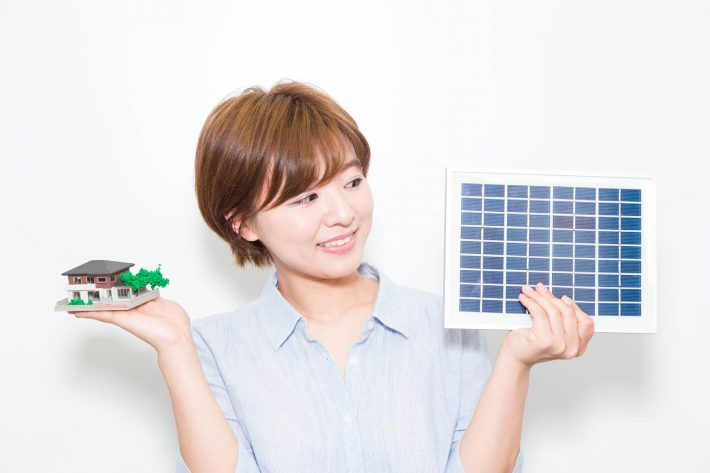 女性が家と太陽光パネルの絵を持っている画像