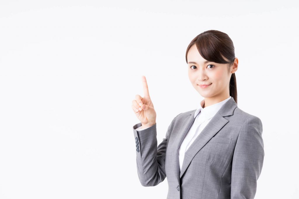 スーツの女性が人差し指を立てている画像