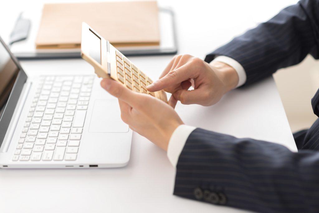パソコンの前で電卓を使い計算しているスーツの男性
