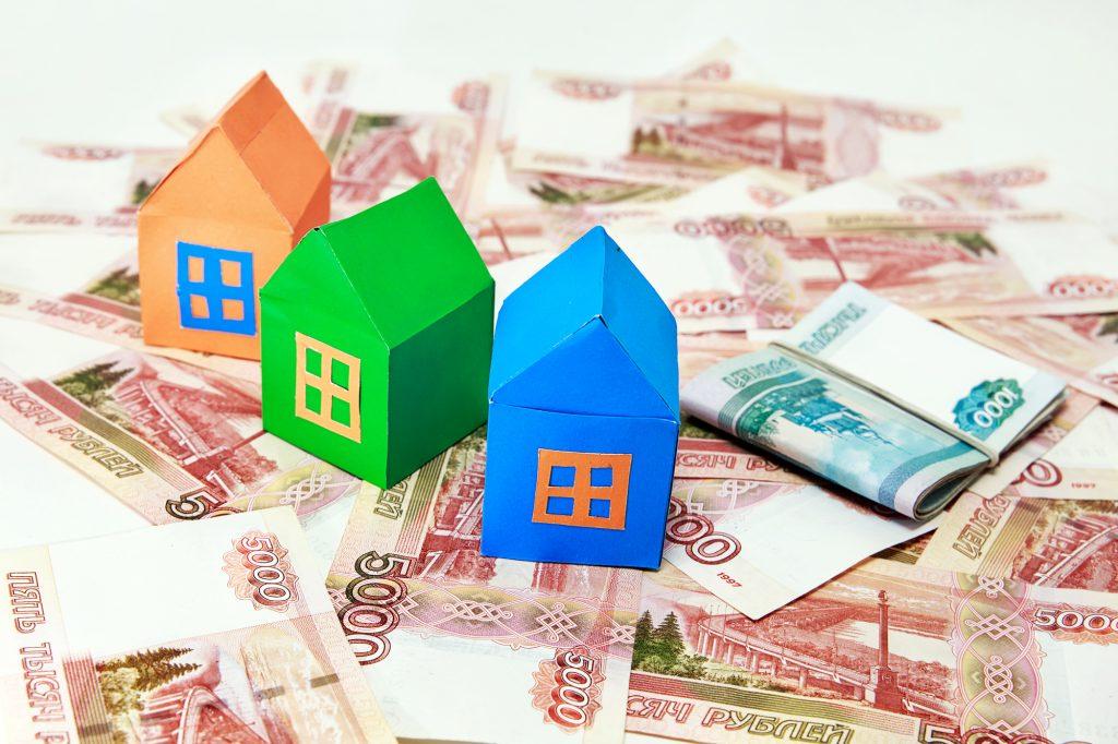 紙幣の上に家の模型が置いてある画像