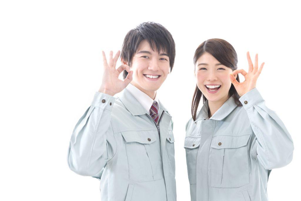 作業着の男女が笑顔でオッケーサインをしている画像